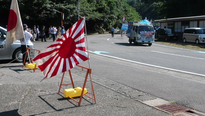 Japanese groups supporting dolphin hunts watch protestors in Taiji, Wakayama Prefecture